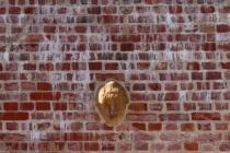 Heřmánkovice - hřbitovní zeď s kříži a kamennou maskou