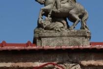 Brány a čelní zdi mají často sochařskou výzdobu. Zde sv. Jiří. Velká Ves