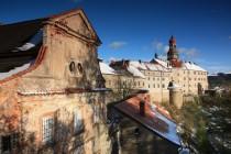 Zámecký areál zcela vyplňuje temeno skalnatého návrší nad centrem města