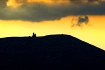 Slunce zapadá nad nejvyšším hřebenem západních Krkonoš. Kromě nápadné siluety vysílače Wawel nad Sněžnými jámami je dobře viditelná i památná mohyla na vrcholu Vysokého Kola.